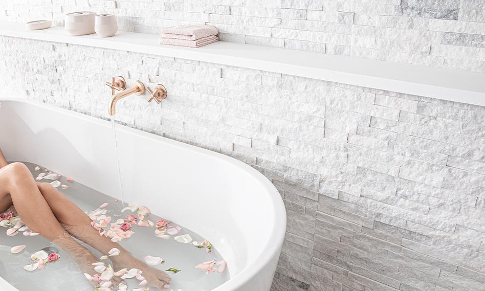 Bain parsemé de fleurs et eau qui coule du robinet dans la baignoire