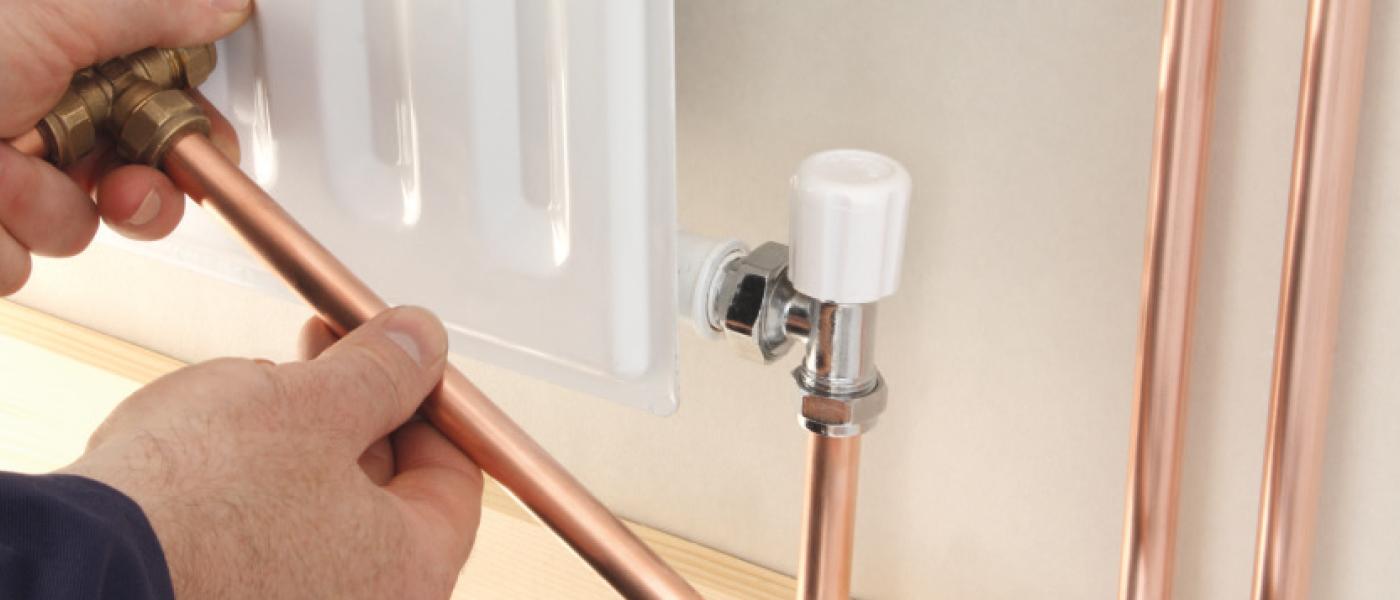 Un plombier-chauffagiste installe un radiateur chez son client.