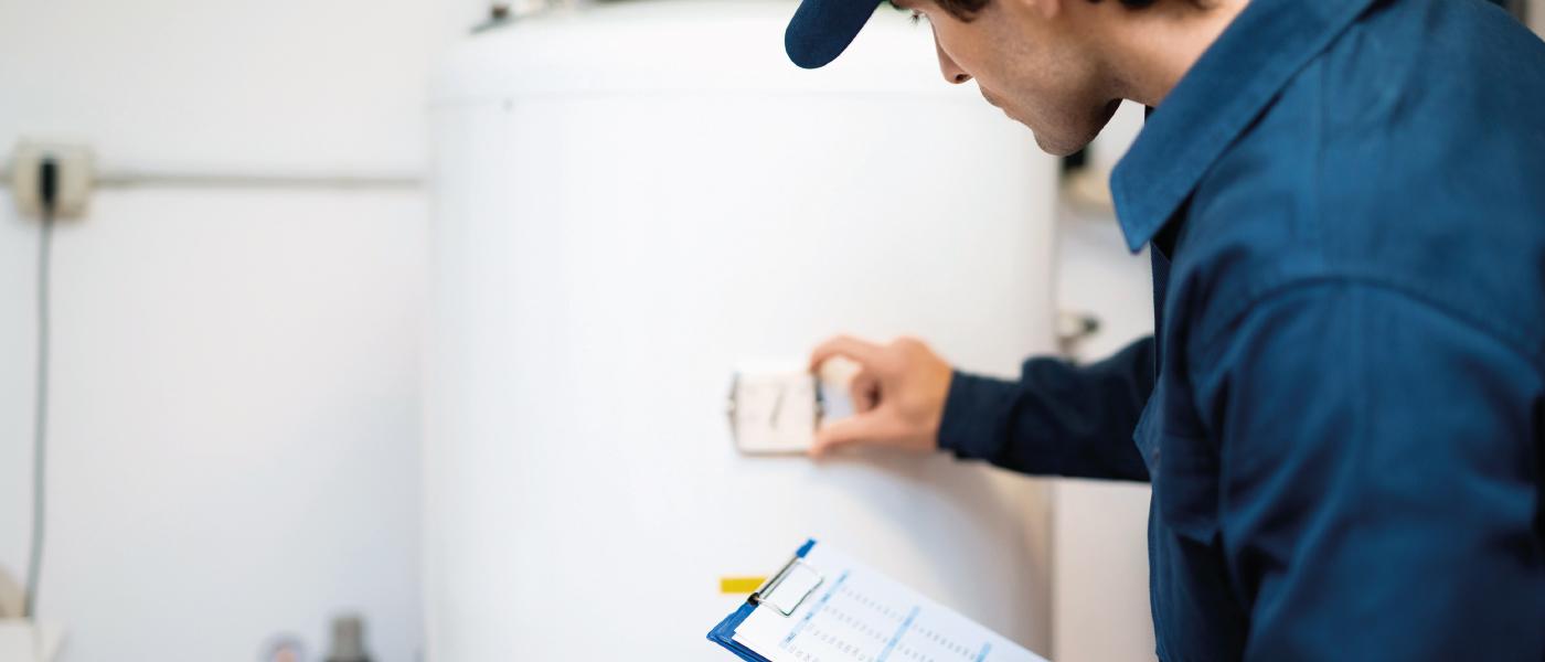 Un plmobier chauffagiste colle une étiquette énergie sur la chaudière d'un client.
