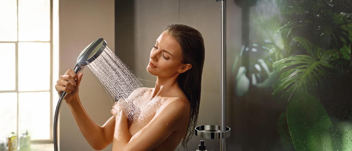Jeune femme prenant une douche, pomme de douche en main