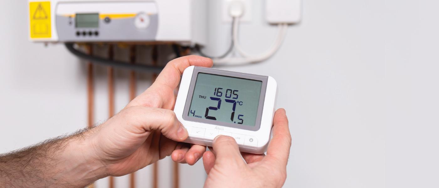 Ouvrier programmant le thermostat Altech et le reliant à une chaudière.